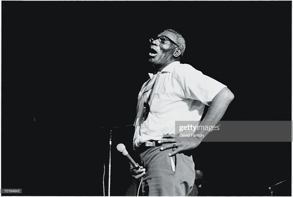 American blues singer and musician Howlin' Wolf holds a microphone and stands on a darkened stage with his hand on his hip as he performs at the Fillmore East, New York, New York, October 9 or 10, 1971.