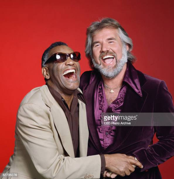 American blues singer Ray Charles and country music singer Kenny Rogers embrace one another as they have a laugh, 1980.
