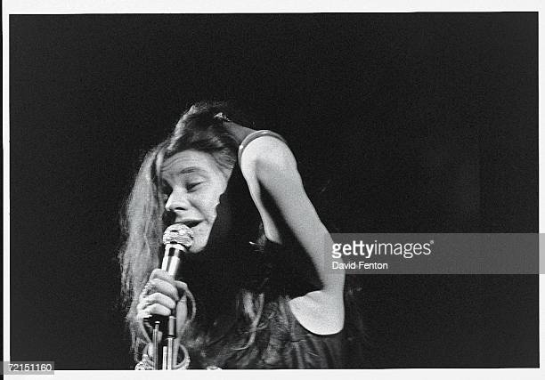 American bluesinfluenced rock singer Janis Joplin runs her fingers through her hair as she sings into a microphone on a darkened stage at the...