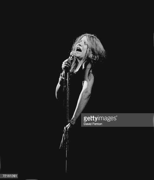 American bluesinfluenced rock singer Janis Joplin sings with passion into a microphone as she performs with her eyes closed on a darkened stage at...