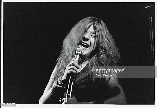 American bluesinfluenced rock singer Janis Joplin sings with passion into a microphone with her eyes closed as she performs on a darkened stage at...