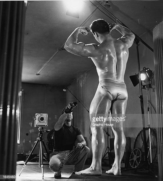 American bodybuilder and physical fitness expert Jack La Lanne wearing a swimsuit poses while photographer Russ Warner sets up a studio portrait with...
