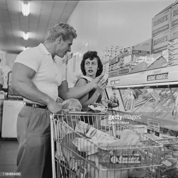 American bodybuilder Jack Delinger , winner of the Mr Universe 1956 contest, out shopping with his wife Loretta and their son John, 1956.
