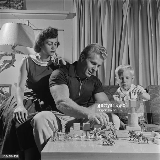American bodybuilder Jack Delinger , winner of the Mr Universe 1956 contest, playing at home with his wife Loretta and their son John, 1956.