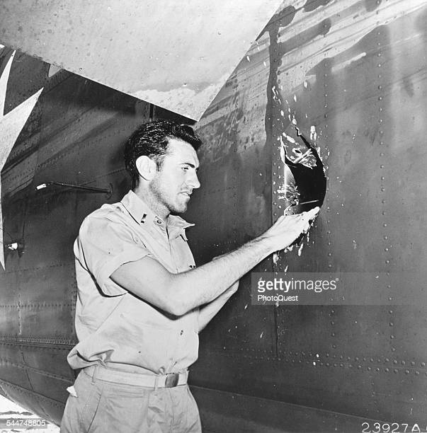 American bombadier Lt Louis Zamperini examines damage in the fuselage of his B-24 Liberator, Funafuti, Ellice Island , May 1943. The hole was caused...