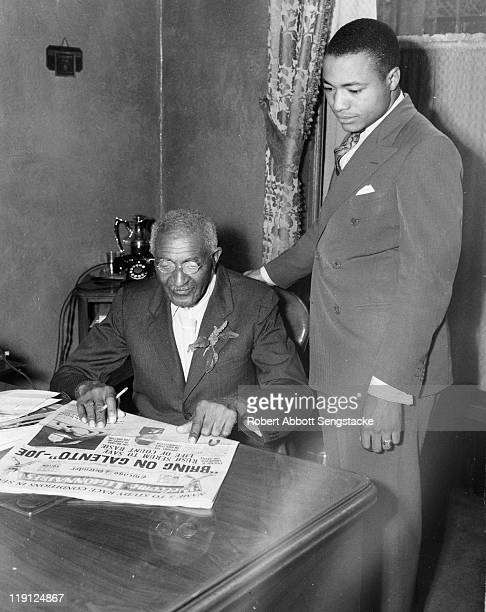 American botanist and educator George Washington Carver sits reading a copy of the Chicago Defender newspaper while publisher John Henry Sengstacke...