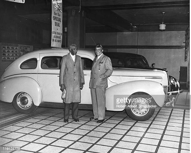 American botanist and educator George Washington Carver stands with an unidentified man at a car dealership 1939 The banner above them reads 'Get Our...
