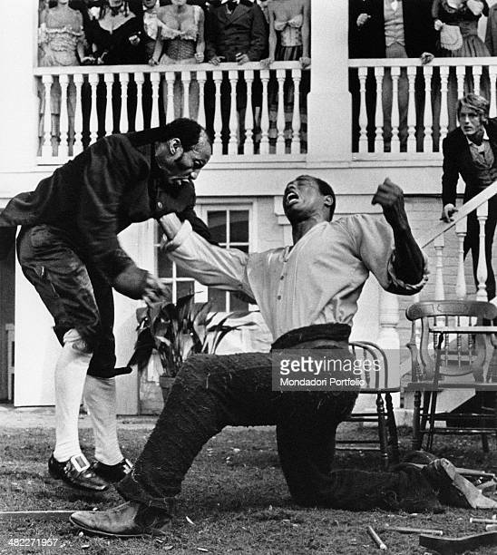 American boxer and actor Ken Norton punching American wrestler and actor Earl Maynard in the film Mandingo Behind him American actor Perry King...