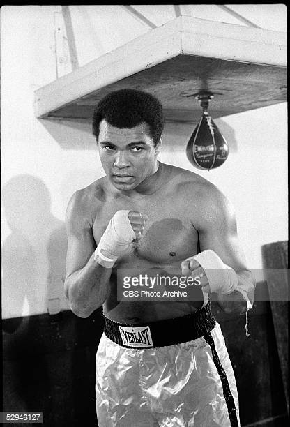 American boxer and sometime actor Muhammad Ali appears in his boxing trunk and poses in his defensive stance with his hands wrapped in bandages 1975...
