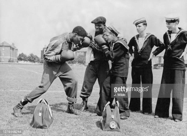 American boxer Frank Daniels sparring with Sea Cadet Jim MacDonald, watched by American lightweight boxer Wallace Smith and two uniformed Sea Cadets...
