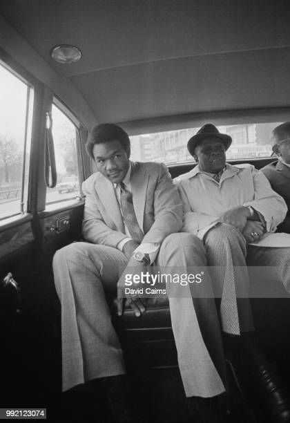 American boxer George Foreman sitting in the backseat of a car with his manager, 13th March 1973.