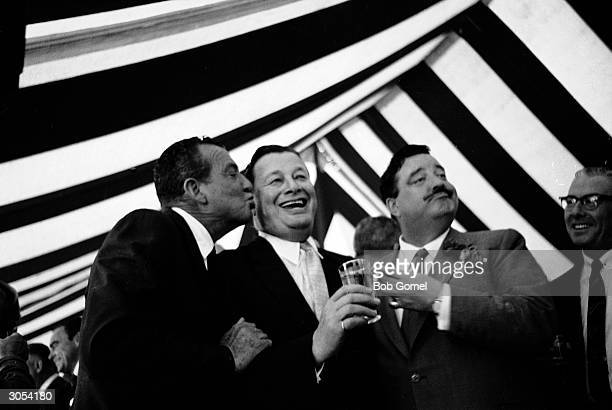 American boxer Jack Dempsey leans in to kiss American restauranteur Bernard Toots Shor on the cheek while American actor and comedian Jackie Gleason...