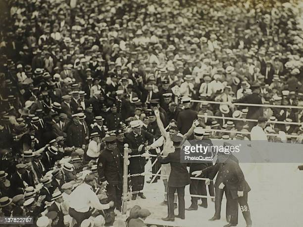 American boxer Jack Dempsey raises his arms in vicotry after defeating French boxer Georges Carpentier in the ring at at Boyle's Thirty Acres Jersey...