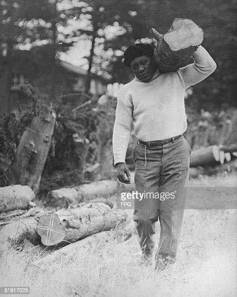 American boxer Jack Johnson hauls wood on his shoulder early 1920s