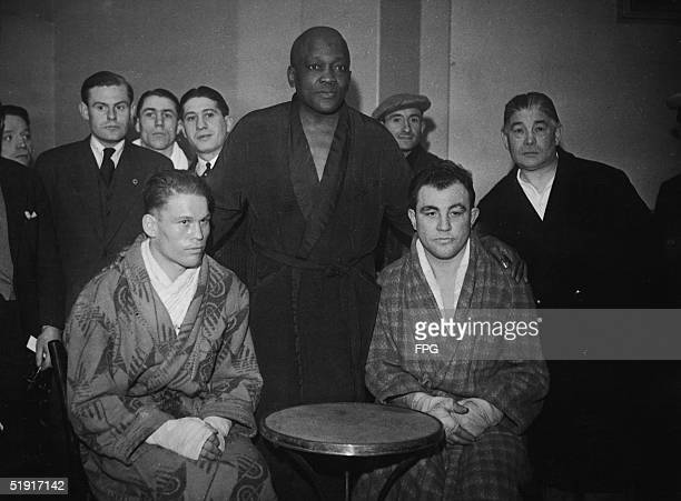 American boxer Jack Johnson poses with French boxer Maurice Griselle and an unidentified boxer probably at an an exhibition match where Johnson and...