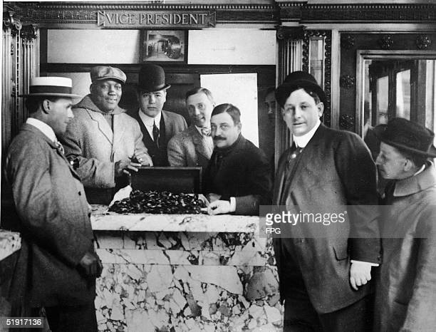 American boxer Jack Johnson the world heavyweight champion and his manager George Little open a chest of coins at a bank late 1900s to early 1910s