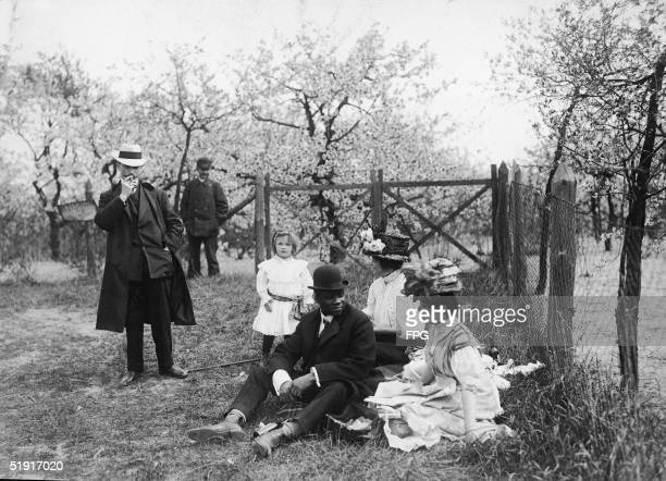 American boxer Jack Johnson the world heavyweight champion on a picnic with an unidentified party among orchard blossoms Berlin Germany mid 1910s