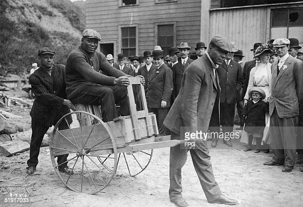 American boxer Jack Johnson the world heavyweight champion rides in a cart past spectators on the street San Francisco California early 1910s