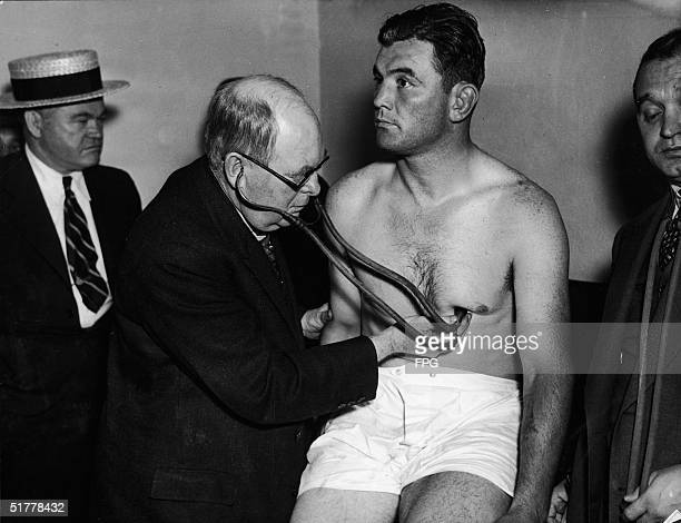 American boxer James Braddock sits in his shorts as Dr William Walker listens to his heart during a medical checkup the night before the heavyweight...
