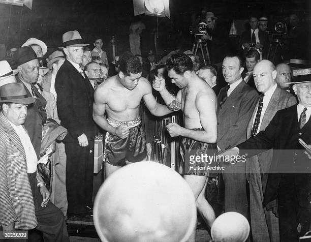 American boxer Joe Louis world heavyweight boxing champion and his challenger German boxer Max Schmeling square off without gloves for newsreel...