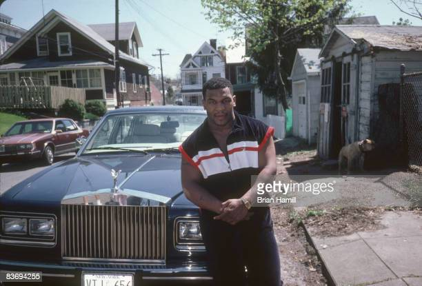 American boxer Mike Tyson poses in front of a Rolls Royce parked on a side street New York April 1987