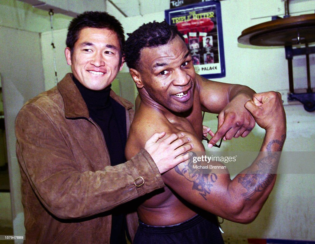American boxer Mike Tyson (right) with Japanese soccer star Kazuyoshi Miura in Las Vegas, Nevada, 9th January 2000. Tyson is training for his Jan 29 fight against Julius Francis. Here he shows off his tattoos of Chairman Mao and a tiger.