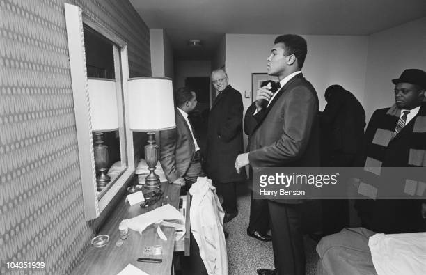 American boxer Muhammad Ali in his hotel bedroom with members of his entourage 15th February 1967