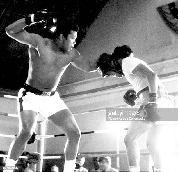 American boxer Muhammad Ali lines up a punch as he spars with an unidentified boxer during a training session 1967