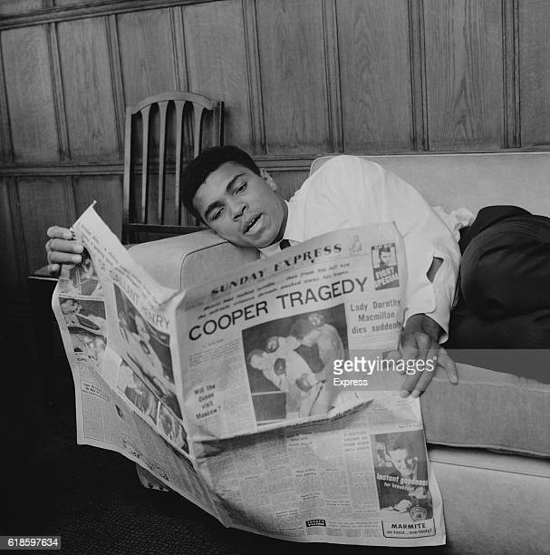 American boxer Muhammad Ali reading the Sunday Express newspaper in his hotel room London UK 22nd May 1966 The headline 'Cooper Tragedy' refers to...