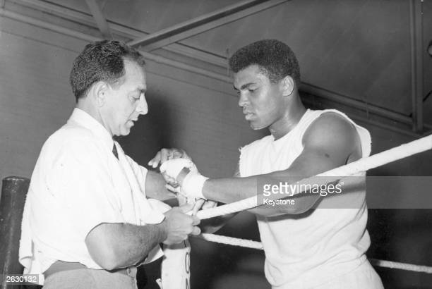 American boxer Muhammad Ali the world heavyweight champion has his hands bandaged by his manager Angelo Dundee before the day's training session at...