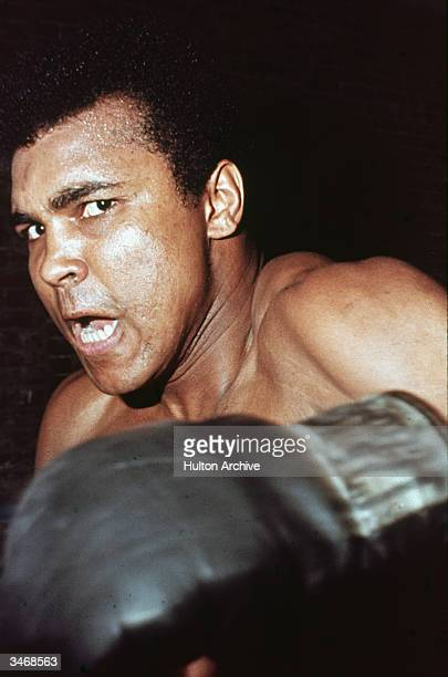 American boxer Muhammad Ali with a fierce expression on his face winds up a punch early 1970s
