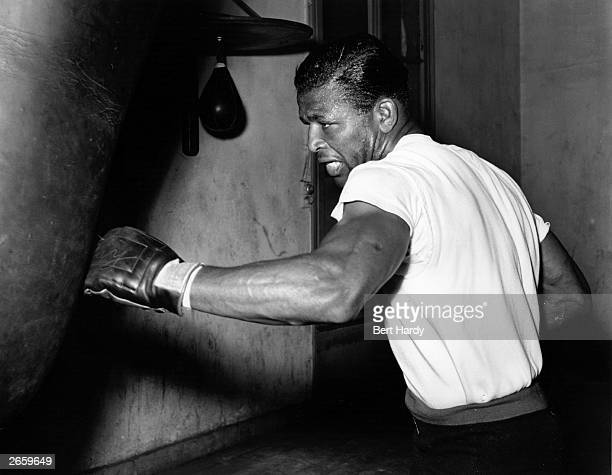 American boxer Sugar Ray Robinson in training with a punch bag at Roger Oquinarenne's gymnasium in Paris for his world middleweight fight against...