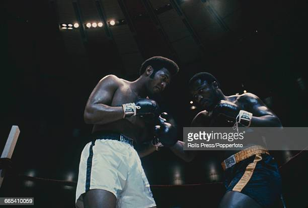 American boxers Jimmy Ellis wearing white shorts and Joe Frazier wearing dark shorts pictured together in mock fight pose at Madison Square Garden in...
