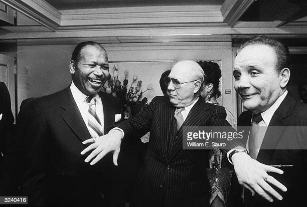 American boxers Sugar Ray Robinson and Jake LaMotta joke as they are separated by one of the guests during Robinson's birthday party at the Carlyle...