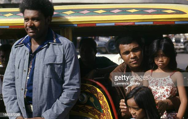 American boxing promoter Don King and boxer Muhammad Ali pose in a colorfully painted vehicle with several unidentified children as they tour Manila...