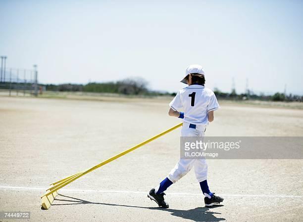 american boy wearing uniform of baseball cleaning up field - sports uniform ストックフォトと画像
