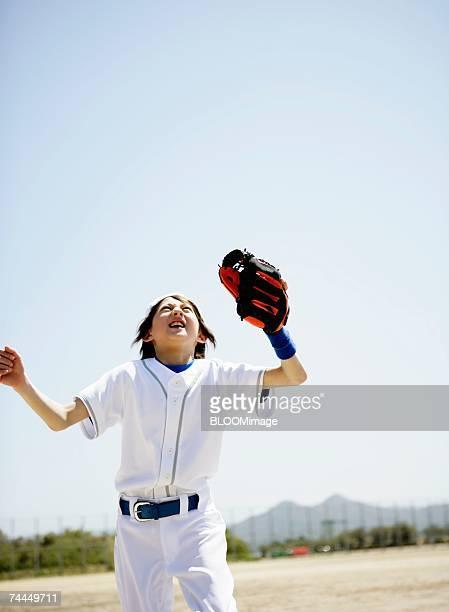 american boy wearing uniform of baseball receiving a ball - sports uniform ストックフォトと画像