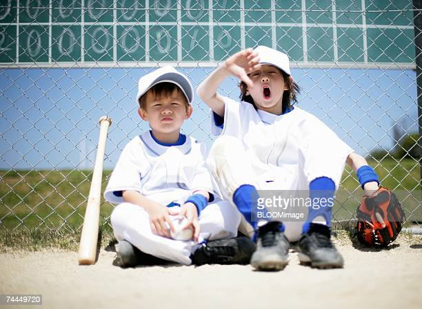 American boys wearing uniform of baseball sitting in front of fence