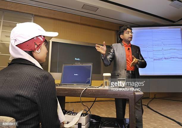 American brain science venture NeuroFocus CEO Pradeep displays an examinee's brain waves chart as she watches a commercial film wearing a EEG headset...