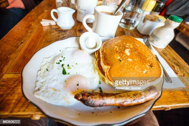 American breakfast with Pancakes, over-easy fried eggs and sausage