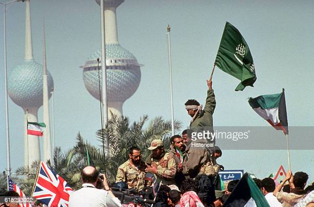 American British Saudi and Kuwaiti flags are held aloft by celebrating soldiers and civilians following the retreat of Iraqi forces from Kuwait as a...