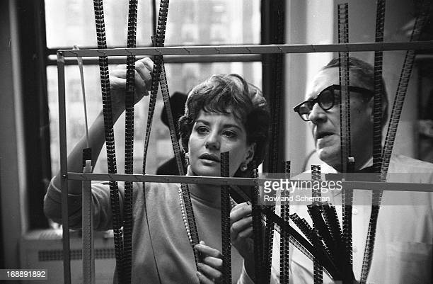 American broadcast journalist Barbara Walters looks at film negatives with an unidentified man behind the scenes at NBC Studios, New York, New York,...