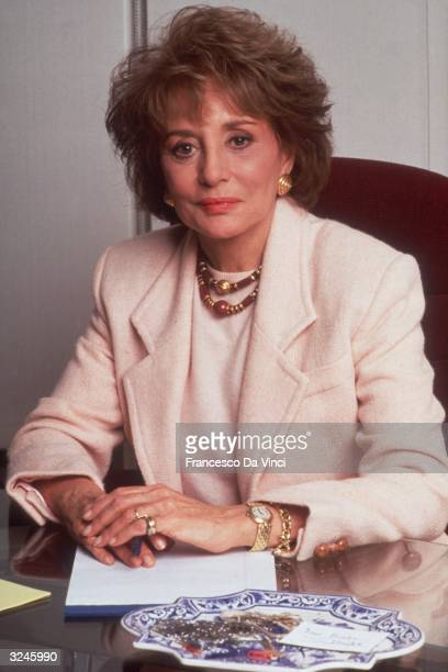 American broadcast journalist Barbara Walters poses at a desk with a notepad and pen.