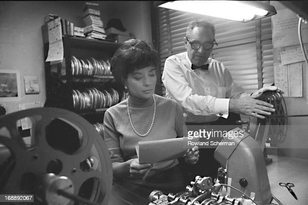 American broadcast journalist Barbara Walters reviews a script as an unidentified man threads a projector at NBC Studios, New York, New York, 1966....