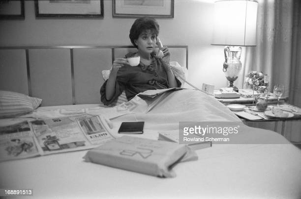 American broadcast journalist Barbara Walters talks on the telephone as she holds a cup of coffee in bed, New York, 1966.