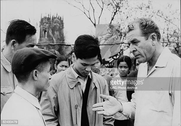 American broadcast journalist Charles Collingwood of CBS News talks to several Vietnamese civilians near a bomb damaged church and a propaganda...