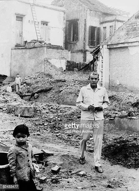 American broadcast journalist Charles Collingwood of CBS News walks through rubble near Vietnamese children in a section of the city bombed by...