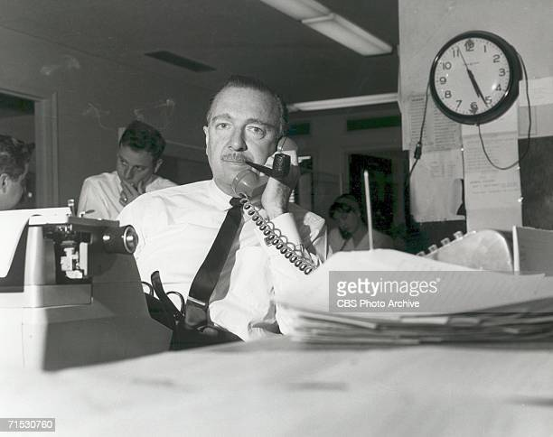 American broadcast journalist Walter Cronkite a pipe in his mouth talks on the telephone in the newsroom New York New York April 29 1963
