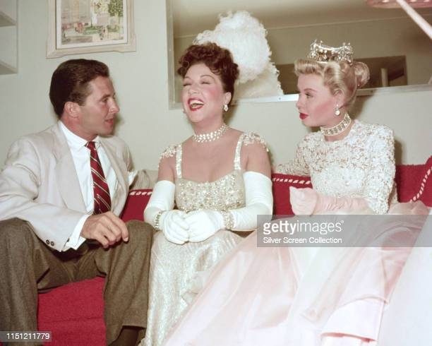 American broadcaster Dean Miller talks to actresses VeraEllen and Ethel Merman who are in costume for their roles in the musical film 'Call Me Madam'...