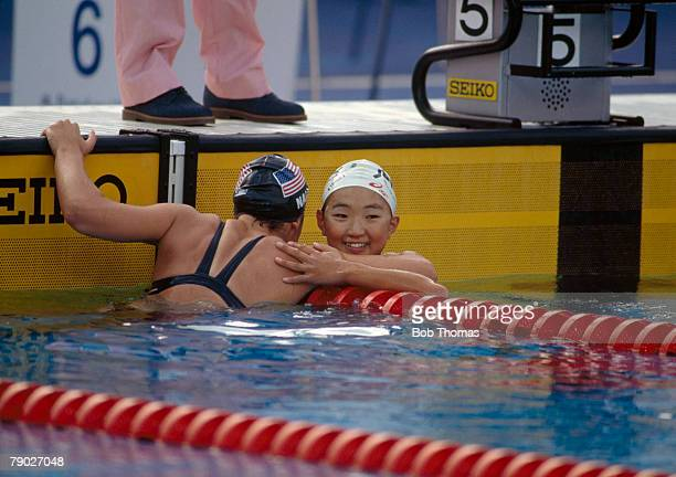 American bronze medal winning swimmer Anita Nall of the United States team reaches over to congratulate Kyoko Iwasaki after the Japanese swimmer...
